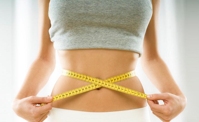 A woman measures her waist